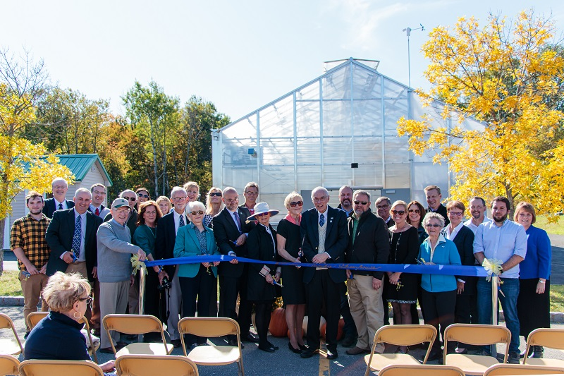 Donors and officials participate in the ribbon cutting.